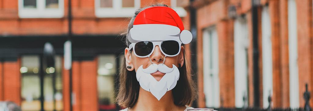 A lady wears a Santa Claus beard with sunglasses on