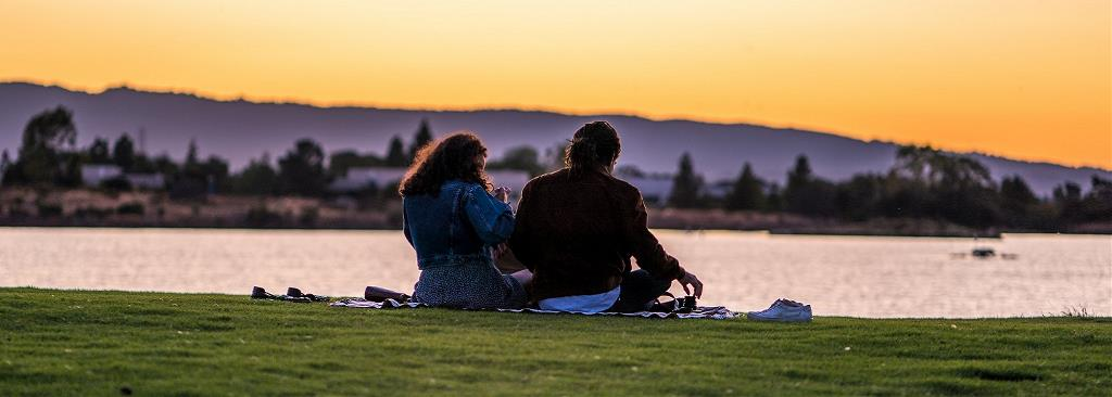 A couple sits on a riverbank looking over the water