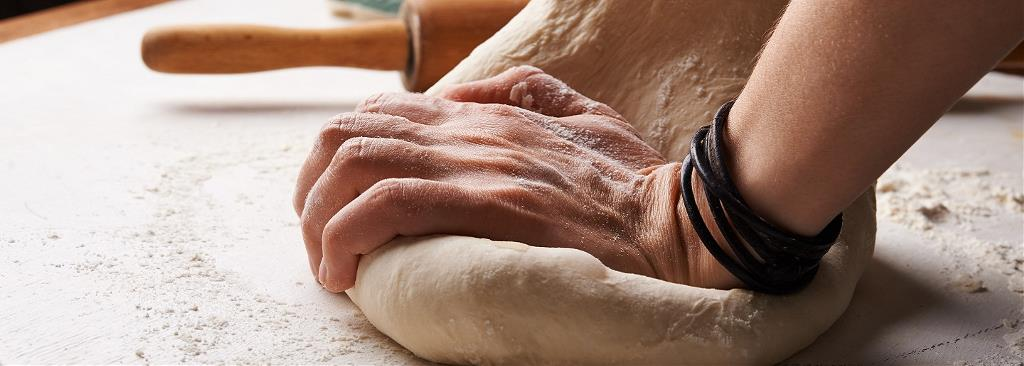 A person kneads the dough whilst making bread
