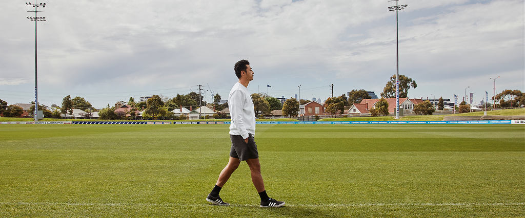 Side angle shot of Lin Jong walking along the boundary line at football oval