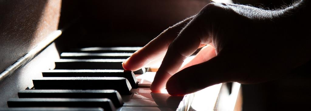 A close-up of a person's hand is shown playing the piano