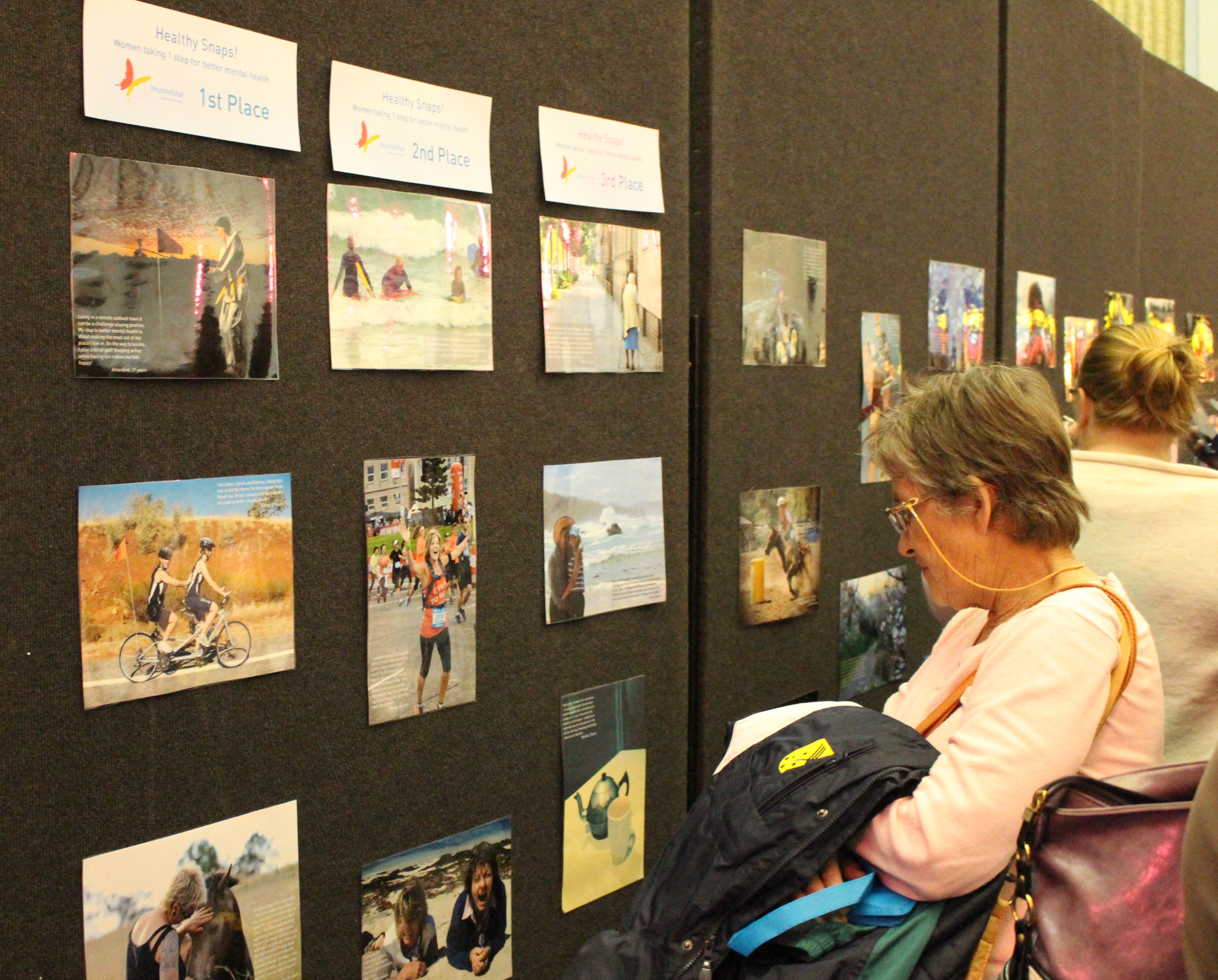 Looking at photos at the exhibition of 'Healthy snaps! Women taking 1 step for better mental health' in Toowoomba.