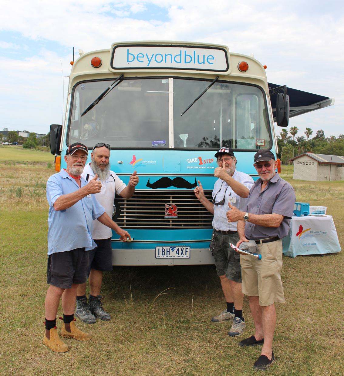 Oxenford Men's Shed members give the thumbs up to moustache growing.