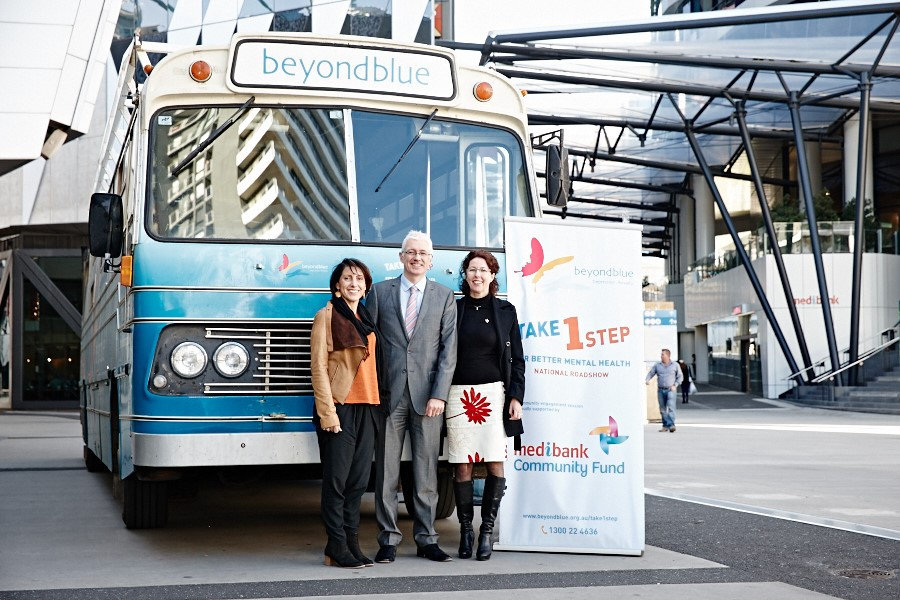 Head of Corporate Social Responsibility at Medibank Rita Marigliani, General Manager of Telephone, Online & Population Health Dermot Roche and Beyond Blue Deputy CEO Susan Anderson with the bus at Docklands.