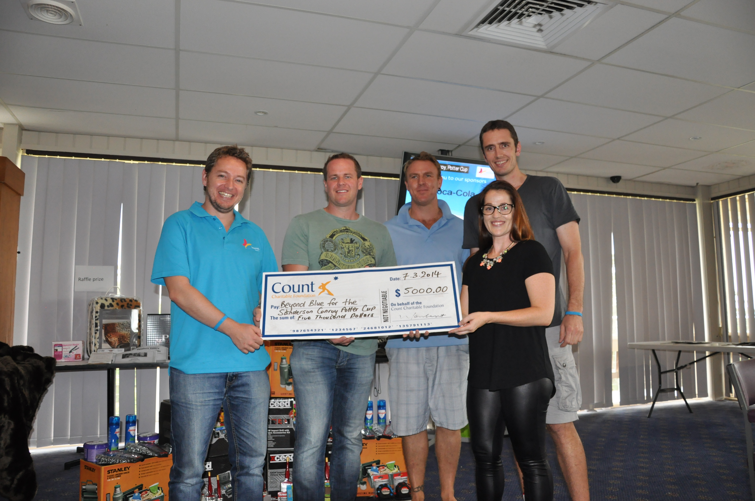 Beyond Blue's Luke, with organisers of the Sanderson Conroy Potter Cup, accepts a cheque from Count Financial.