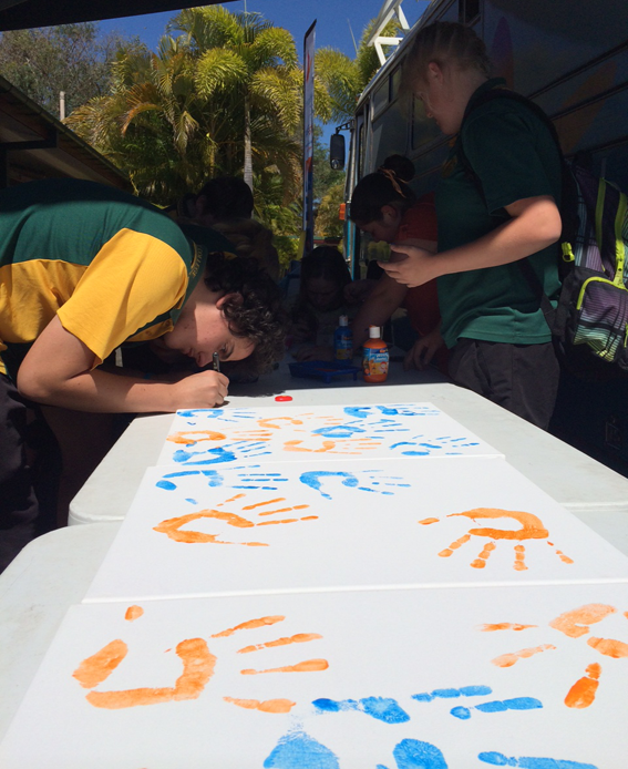 Students at Burnett State College add to the canvas art.